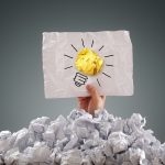 38970065 - businessman buried under crumpled pile of papers with an idea sign